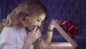 有美丽的卷发的年轻可爱的妇女打开一个发光的礼物盒 影视素材