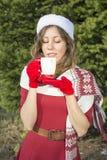 有美丽的圣诞老人的女孩杯子发球区域户外 库存图片