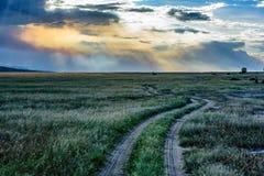 有美丽的天空和云彩的土路在肯尼亚,非洲 免版税库存照片