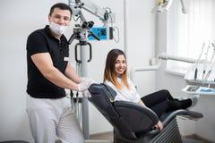 有美丽的女性患者的男性牙医在现代牙齿诊所的治疗以后 坐在牙齿椅子的妇女 图库摄影