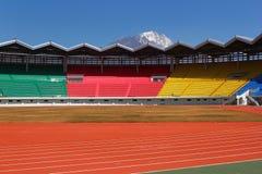 有美丽的山的新的空的五颜六色的体育场在背景中 库存照片