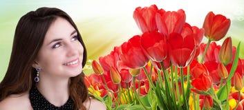 有美丽的庭院新鲜的五颜六色的郁金香的秀丽女孩 库存图片