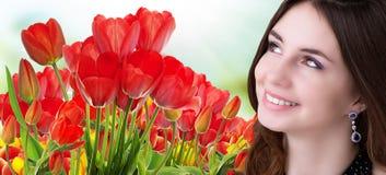 有美丽的庭院新鲜的五颜六色的郁金香的秀丽女孩 免版税库存图片