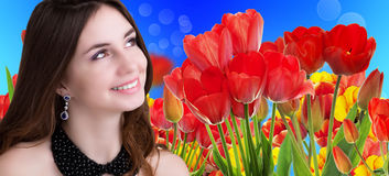 有美丽的庭院新鲜的五颜六色的郁金香的秀丽女孩 免版税图库摄影