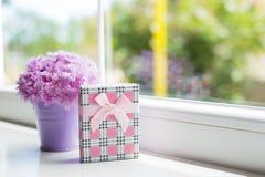 有美丽的桃红色康乃馨嫩花束的一点紫色桶与礼物盒的在窗口附近在白天 库存图片