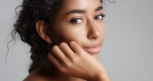 有美丽的橄榄色的皮肤和卷发理想的皮肤和褐色眼睛的愉快的平静的少妇在演播室 库存图片