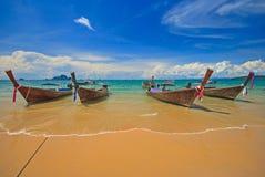 有美丽的沙滩的泰国传统木longtail小船和在Ao Nang海滩,甲米府,T的五颜六色的多云天空蔚蓝背景 免版税库存照片