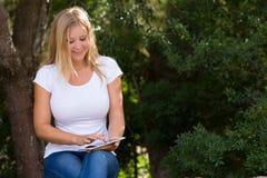 有美丽的白肤金发的少妇室外互联网的覆盖面 免版税库存照片