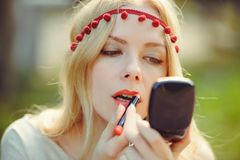 有美丽的白肤金发的平直的长的染发剂的被提炼的嫩少妇她的嘴唇和神色在镜子在自然 种族clothi 免版税库存图片