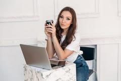 有美丽的眼睛和长的头发的一个甜嫩女孩微笑并且坐工作在咖啡馆的一台计算机,拿着杯子  库存图片