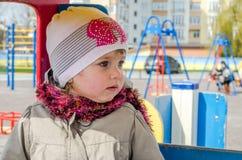 有美丽的眼睛的可爱的小女孩婴孩,使用在木摇摆在游乐园,在有敞篷的一件雨衣穿戴了, 库存照片