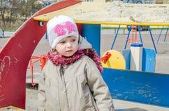 有美丽的眼睛的可爱的小女孩婴孩,使用在木摇摆在游乐园,在有敞篷的一件雨衣穿戴了, 免版税库存图片