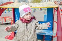 有美丽的眼睛的可爱的小女孩婴孩,使用在木摇摆在游乐园,在有敞篷的一件雨衣穿戴了, 图库摄影