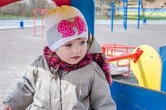有美丽的眼睛的可爱的小女孩婴孩,使用在木摇摆在游乐园,在有敞篷的一件雨衣穿戴了, 免版税库存照片