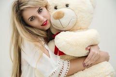 有美丽的眼睛的可爱的白肤金发的女孩坐她的床和拥抱玩具熊 轻的白色礼服的妇女 性感的夫人 免版税库存图片