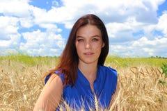 有美丽的眼睛的妇女在麦田 免版税库存图片