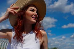有美丽的红色头发的微笑的妇女在帽子 免版税库存图片