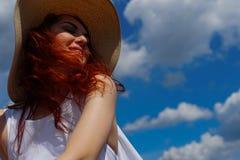有美丽的红色头发的微笑的妇女在帽子 免版税图库摄影