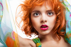 有红色头发和五颜六色的礼服的女孩在白色 库存图片