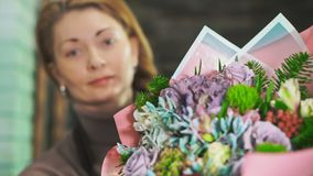 有美丽的花束的妇女卖花人 在前景的花束有被弄脏的背景