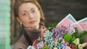有美丽的花束的妇女卖花人 在前景的花束有被弄脏的背景 股票录像