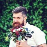 有美丽的花束的英俊的有胡子的人 3花束重点前景婚礼 拿着花的时髦的有胡子的人户外 衣物夫妇日愉快的葡萄酒婚礼 库存照片