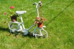 有美丽的花的老白色儿童自行车 免版税库存图片