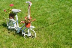 有美丽的花的老白色儿童自行车 库存照片