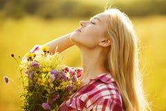 有美丽的花花束的愉快的女孩  免版税库存照片