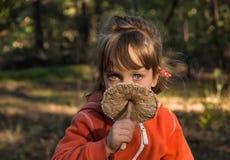 有美丽的蓝眼睛的五年老女孩拿着遮阳伞mushr 免版税库存图片