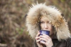 有美丽的蓝眼睛的白肤金发的妇女喝咖啡的 库存图片