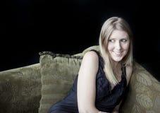 有美丽的蓝眼睛的白肤金发的妇女在绿色沙发 免版税库存图片