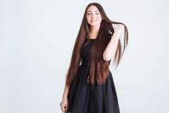 有美丽的长的黑发的可爱的妇女在黑礼服 免版税图库摄影