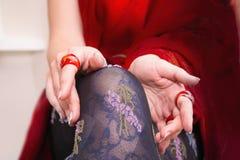 有美丽的长袜的Woman's有红色圆环的腿和手 免版税库存照片