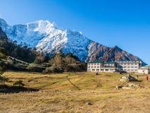 有美丽的雪的小村庄加盖了山背景 免版税库存图片