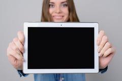 有美丽的面孔的妇女,暴牙的微笑显示有空的黑屏幕的数字式片剂 关闭照片,隔绝在灰色backgr 免版税库存照片