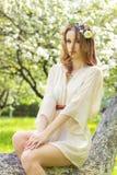有美丽红色的头发的美丽的年轻性感的女孩用在她的头发的花组成,坐在一棵树在一棵豪华的苹果树 库存图片