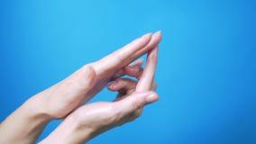有美丽自然修指甲移动的柔和的女性手在蓝色背景 E 股票录像