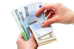 有美元和欧元的手 图库摄影