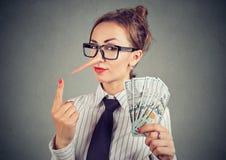 有美元现金和狡猾的神色的说谎者女实业家 免版税库存图片