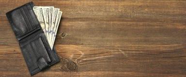 有美元现金的人的钱包在概略的木背景 库存照片