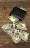 有美元现金的人的钱包在概略的木背景 免版税库存照片