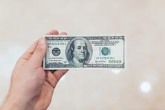 有美元的一个人在她的手上 背景查出的白色 库存图片