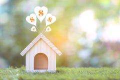 有美元的气球和标志的式样房子在自然绿色背景的,存金钱为准备今后和银行业务概念 免版税图库摄影