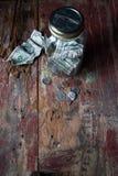 有美元的金钱在老木桌上的瓶子和变动 库存照片