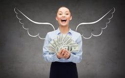 有美元金钱和天使翼的女实业家 库存图片