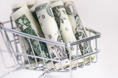 有美元钞票的充分的购物台车在白色背景 查出 消费者至上主义和金钱的概念 库存图片