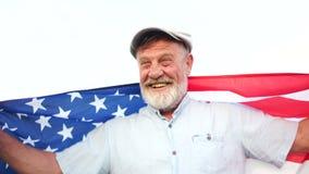 有美国各州旗子的美国退休的爱国者在他的手上 美国独立日的庆祝 盖帽和灰色的一个人 股票视频