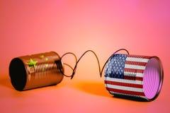 有美国和中国旗子的锡罐电话 黑色通信概念收货人电话 图库摄影