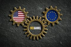 有美国和欧盟旗子和词的'自由贸易'三个钝齿轮用德语在中部 免版税库存图片